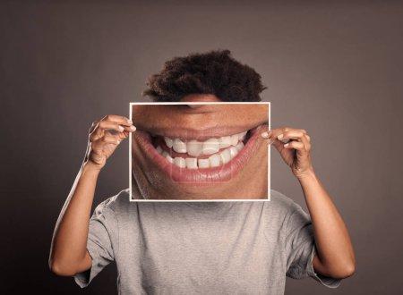 Photo pour Femme noire tenant une photo d'une bouche souriante sur un fond gris - image libre de droit
