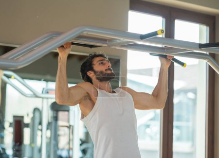 Man doing free body calisthenic pull-ups in a gym