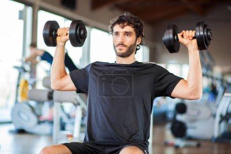 Photo pour Homme assis sur un banc avec haltères en gym - image libre de droit