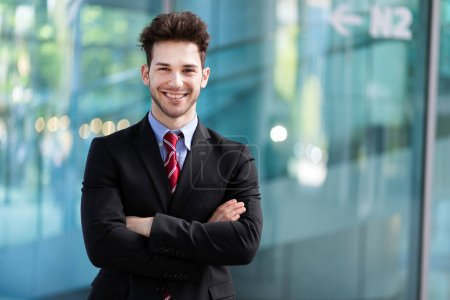 Photo for Young businessman in the city with crossed arms - Royalty Free Image