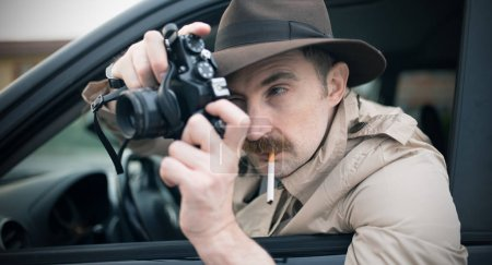 Spy or paparazzo photographer, man using camera in...
