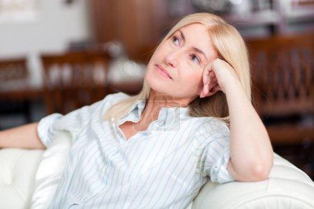 Photo pour Belle femme blonde d'âge moyen assise sur un canapé à la maison - image libre de droit