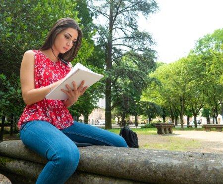 Photo pour Femme étudiant en étant assise à l'extérieur - image libre de droit