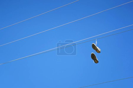 Old sneaker shoes hanging on an electric cable against blue sky