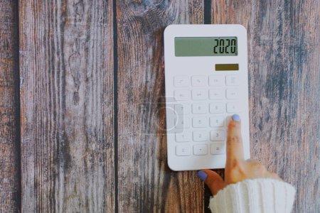 Photo pour Femme main sur blanc calculatrice sur fond en bois, résolutions du nouvel an sur les finances, planification budgétaire pour 2020 concept - image libre de droit