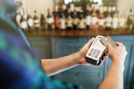 Hand of customer paying with contactless credit card with NFC technology.