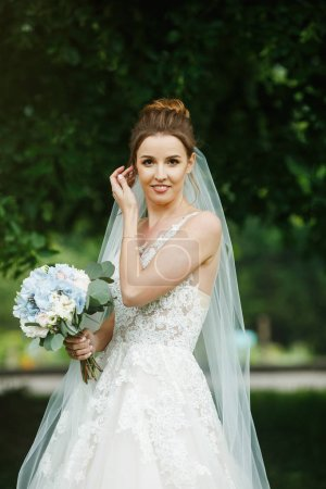 Pretty happy bride in luxury dress with bouquet of roses.