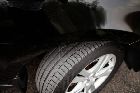 Car wheel close-up. Black modern car closeup.