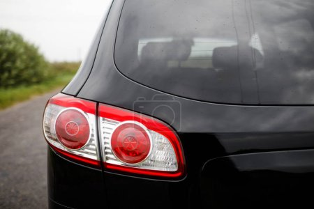 Photo for Back view of new black car. Closeup headlights of car. Black premium city crossover, luxury SUV rear light closeup. Car lamp close-up. - Royalty Free Image
