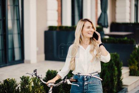 Photo pour Belle fille en vélo utilisant un téléphone. Femme sexy avec vélo vintage dans le parc . - image libre de droit