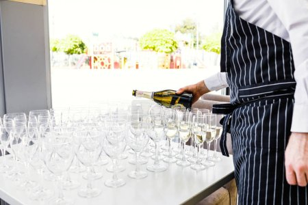 Photo for Wedding alcohol drink bar. Waitress pouring champagne into a glass on a wedding celebration. - Royalty Free Image