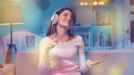 Photo pour Portrait de femme heureuse à la maison est l'écoute de la musique dans les écouteurs - image libre de droit