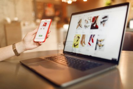 Photo for Online Shopping Concept. Online payment. Woman hand using smartphone and laptop computer for online shopping. Payment Detail page display. - Royalty Free Image