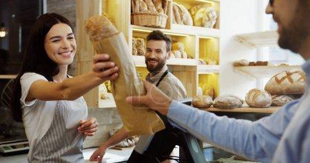 Photo pour Belle femme, vendeuse dans la boulangerie, vendant des baguettes à l'homme tandis que son beau collègue masculin l'aide . - image libre de droit