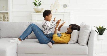 Photo pour Heureuse maman américaine africaine jouant à un jeu drôle avec une petite fille mignonne à la maison. - image libre de droit