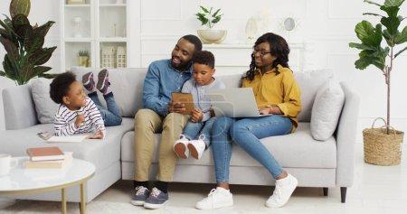 Photo pour Heureuse famille afro-américaine assise sur un canapé avec un appareil à la maison. Mère utilisant ordinateur portable, père et fils tenant tablette numérique, dessin mignon petite fille. Concept du temps familial - image libre de droit