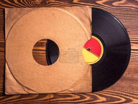 Photo pour Ancien disque vinyle sur la table en bois, mise au point sélective et image tonique - image libre de droit