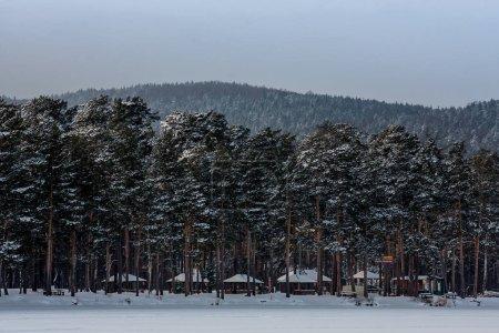 Photo pour Paysage hivernal. air frais glacé sur un lac de montagne. neige claire, pins et arbres sur le rivage montagneux. gazebos pour les loisirs de plein air. kebab cuisson et repos feu de camp . - image libre de droit
