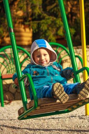 Foto de Sonriendo a feliz niño europeo sentado en un patio de los cabritos colorido. infantiles juguete en el patio de la escuela, volver a la actividad escolar que sube. jardín de la infancia preescolar. - Imagen libre de derechos