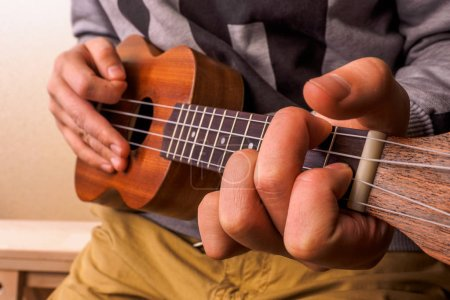 Photo for Closeup of young man hands playing acoustic guitar ukulele. - Royalty Free Image