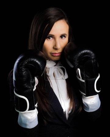 Photo pour Une jeune fille en costume d'employée de bureau met en colère son patron. concept de stress et d'activité. gants de boxe et noirs - image libre de droit
