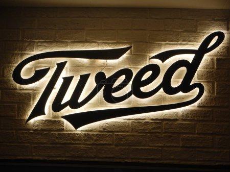 Photo pour Smiths Falls, On, Canada - 25 août 2018 - une image éditoriale prise au Festival Shindig Tweed - signe de Tweed logo allumée sur un mur de briques. - image libre de droit