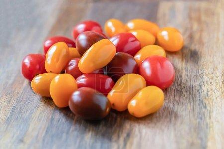 Photo pour Tomates cerises jaunes, rouges et noires sur fond de bois - image libre de droit