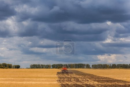 Photo for An orange modern tractor plows the earth i - Royalty Free Image