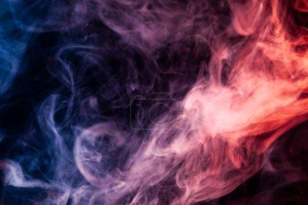 Photo pour Fumée dense multicolore de couleurs bleues, blanches et rouges sur un fond isolé noir. Fond du robinet de fumée - image libre de droit