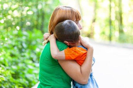 Photo pour Belle femme et son petit fils tremblant et embrassant fortement, sur fond de parc de la ville. Portrait d'été de la mère et du fils à la fête des mères . - image libre de droit