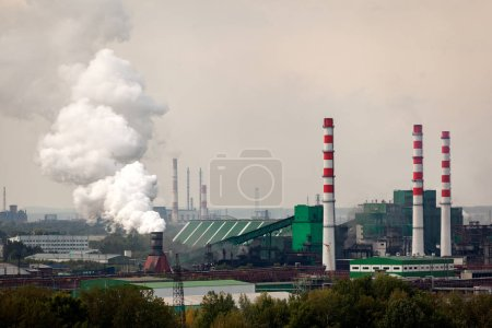 Photo for The landscape of a huge industrial city with factories and high cranes from which come out with huge smoke puffs. Pollution of the environment by plants and industries - Royalty Free Image