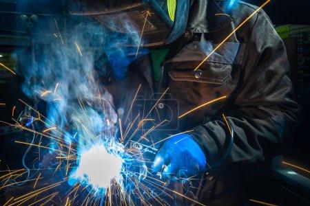 Photo pour Homme soudeur dans le masque de soudage, la construction uniforme et bleu gants de protection soudures silencieux de voiture métallique avec machine de soudage dans l'atelier de réparation automobile, dans le chantier de construction de fond - image libre de droit