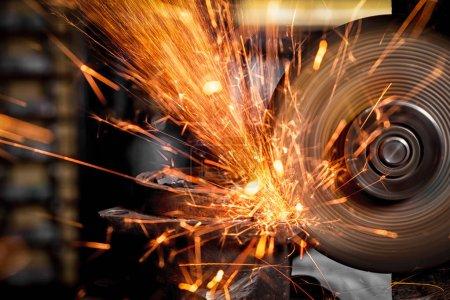 Photo pour Un jeune homme soudeur meuleuse métal une meuleuse d'angle dans l'atelier, étincelles volent sur le côté - image libre de droit