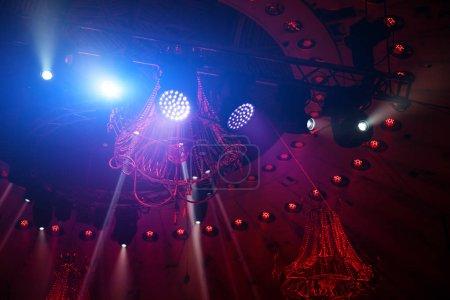 Photo pour Le plafond de la scène théâtrale avec un équipement d'éclairage multicolore. Eclairage. Projecteurs bleus dans le cirque Rayons lumineux multicolores provenant des projecteurs de scène sur scène en fumée pendant un spectacle . - image libre de droit