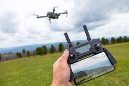 Photo for Landscaping on a quadrocopter. A young man holds in his hand a quadrocopter control panel with a monitor and an image of mountains; in the background is a quadrocopter - Royalty Free Image