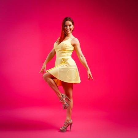 Photo pour Belle femme au corps sain portant une robe dansant et tournant autour sur fond rose.Le concept de vêtements de mode d'été et de détente. humeur rose et joyeuse . - image libre de droit