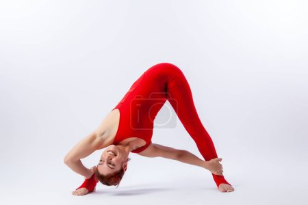 Photo for Beautiful slim woman in sports overalls  doing yoga, standing in an asana balancing pose - parsvottanasana on white  isolated background. The concept of sports and meditation. Training for stretching and yoga - Royalty Free Image