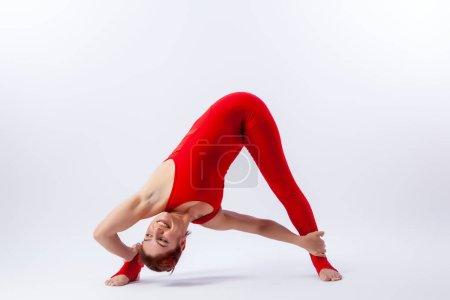 Foto de Hermosa mujer delgada en monos deportivos haciendo yoga, de pie en una pose de equilibrio de asana - parsvottanasana sobre fondo blanco aislado. El concepto de deportes y meditación. Entrenamiento para estiramiento y yoga - Imagen libre de derechos