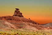 Cowboy on horseback passes by Mexican Hat Rock in Mexican Hat, Utah, USA