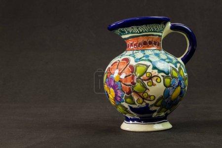 Foto de Un jarrón de talavera con una actitud seria sobre un fondo texturizado negro - Imagen libre de derechos