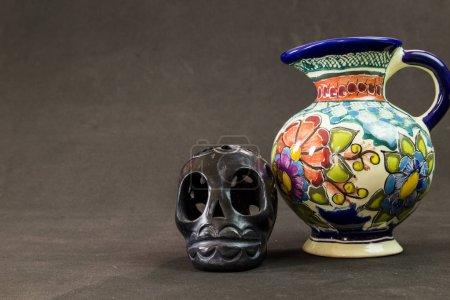 Foto de Un jarrón de Talavera muy grave con un cráneo de Oaxaca negro sobre un fondo negro con textura - Imagen libre de derechos