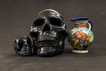 Foto de Un jarrón de Talavera muy grave con un cráneo negro de Oaxaca y un cráneo muy grande de arcilla negra - Imagen libre de derechos