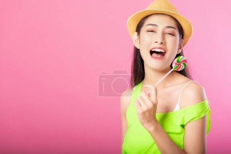 Photo for Portrait of a smiling attractive woman in summer outfit and hat holding lollipop and looking at camera isolated over pink background. - Royalty Free Image