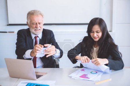 Photo pour Un homme d'affaires arrachant du papier. Homme caucasien principal avec sa belle assistance asiatique assis sur le bureau et détruire les papiers autour. Concept de travail stressant . - image libre de droit