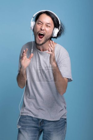 Photo for Young bearded man listening to music in blue background. Very happy Asian young hipster using white headphone to listen and dance to music, half body shot. Young generation hipster concept. - Royalty Free Image