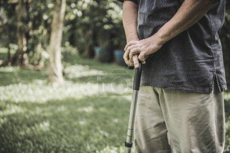 Foto de En el Parque sosteniendo un bastón viejo. Hombre asiático, concepto de estilo de vida senior. - Imagen libre de derechos