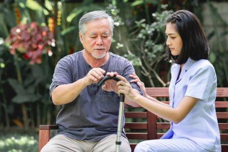 Nurse with patient sitting on bench together talking. Asian old man and young woman sitting together talking. Serious mood.