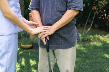Photo for Comforting hand. Young nurse holding old man's hand in outdoor garden. Senior care, care taker and senior retirement home service concept. Close up shot. - Royalty Free Image