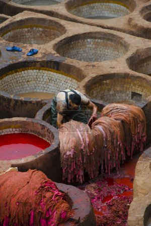 male painting leather in Fez at ancient tanneries in Medina