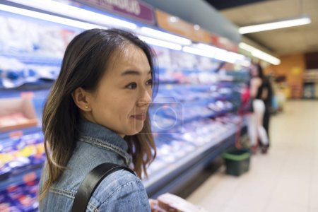 Asiatic woman shopping in a supermarket